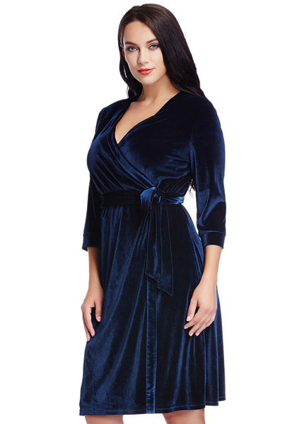 Left angled view of model in plus size navy blue velvet wrap dress