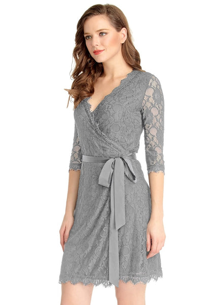 Left angled view of woman wearing grey lace overlay plunge wrap-style dress
