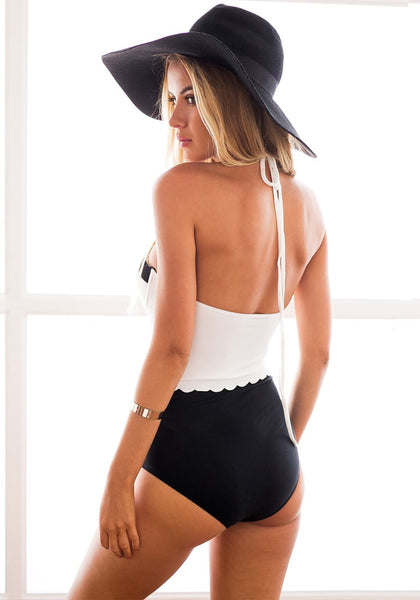 Left back of model in black and white scallop-trim swimsuit