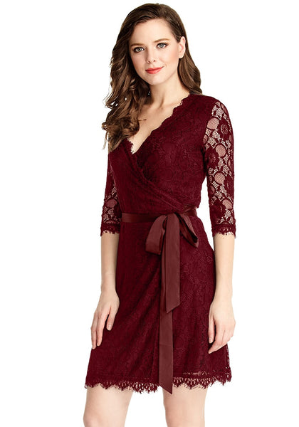 Left side angled view of model in burgundy lace overlay plunge wrap-style dress