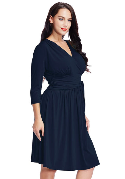 Left side angled view of model in plus size navy blue plunge tie-side wrap dress