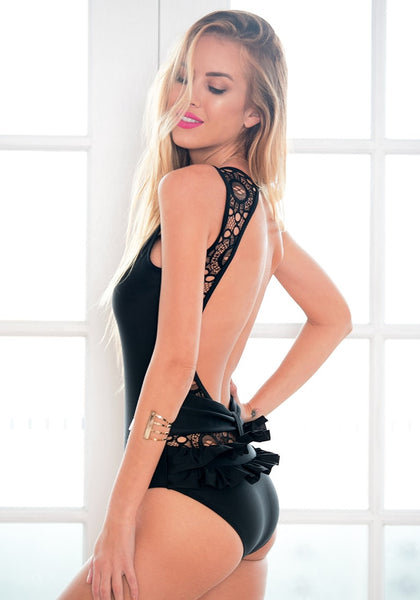 Left side of blonde model in black lace cutout open-back swimsuit