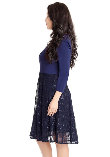 Left side shot of model in navy matte sequins abstract mesh-bottom dress