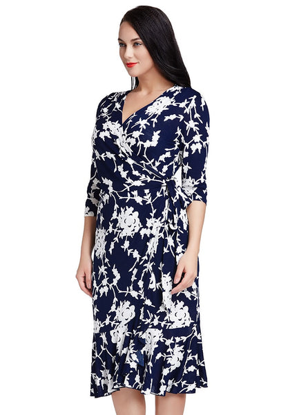 Left side shot of model in plus size blue floral ruffled wrap dress