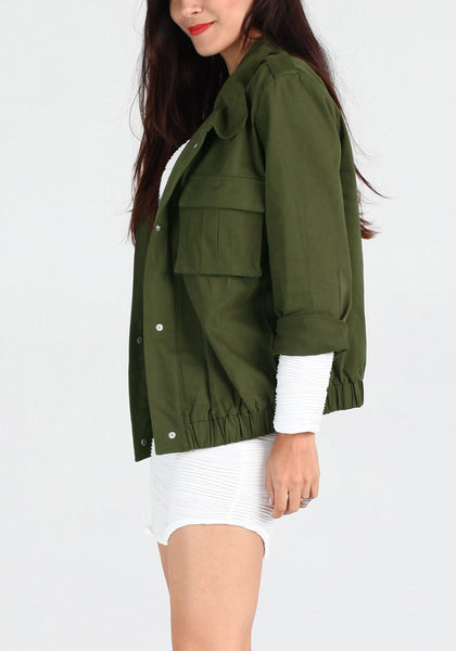Left side view of girl in moss green button-down military jacket