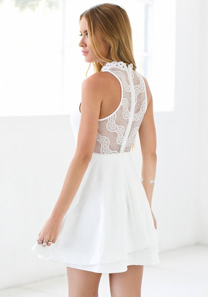 Left side view of lady in white lace illusion neck dress