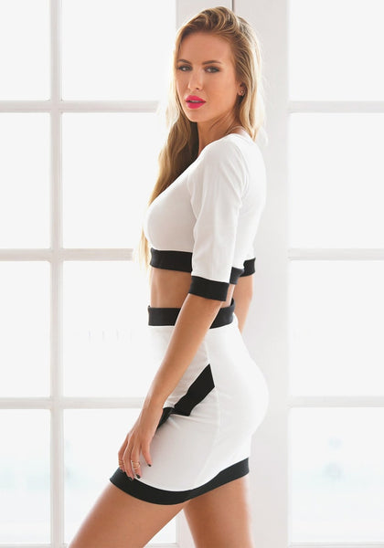 Left side view of model in black-lined white two-piece dress