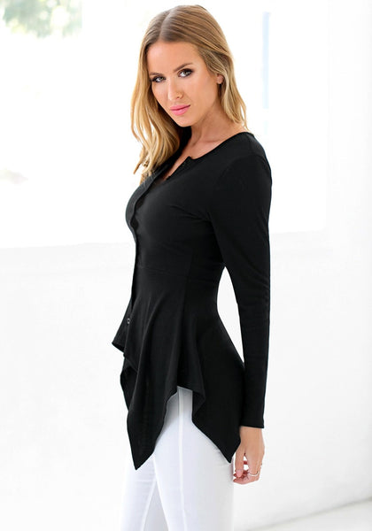 Left side view of model in black asymmetrical knit top