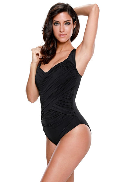 Left side view of model in black crossover ruched swimsuit