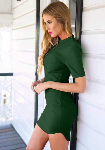 Left side view of  model in dark green curved hem bodycon dress