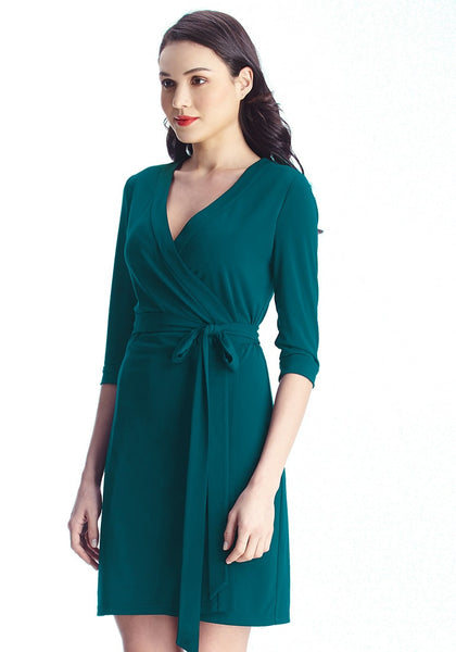 Left side view of model in deep sea wrap-style belted dress