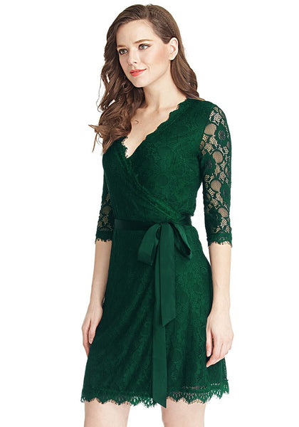 Left side view of model in green lace overlay plunge wrap-style dress