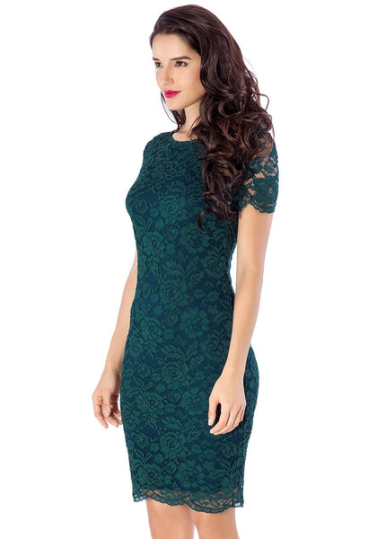 Left side view of model in green lace overlay shift dress