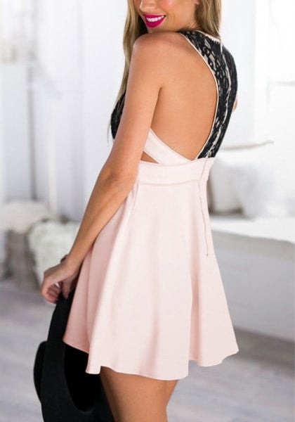 Left side view of model in light pink plunge skater dress