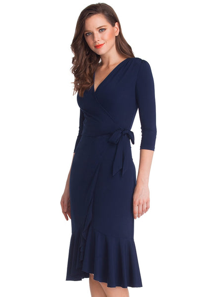 Left angle shot of woman in navy blue asymmetrical ruffled wrap dress