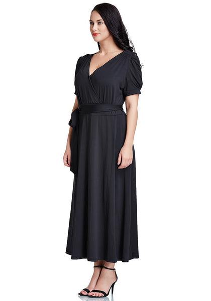 Left side view of model in plus size black surplice belted long dress