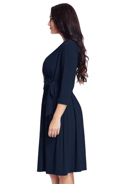 Left side view of model in plus size navy blue plunge tie-side wrap dress