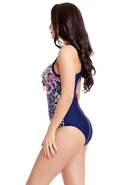 Left side view of model in plus size navy printed swimsuit