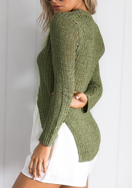 Left side view of model in verdigris green high-low knit sweater with right hand placed at the back
