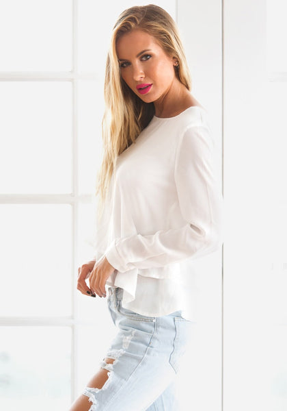 Left side view of model in white layered chiffon blouse