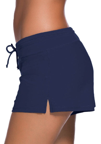 Left side view of model wearing royal blue drawstring side-slit board shorts