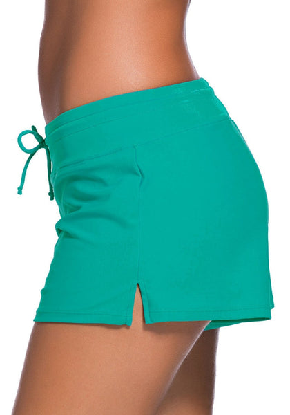 Left side view of model wearing turquoise drawstring side-slit board shorts