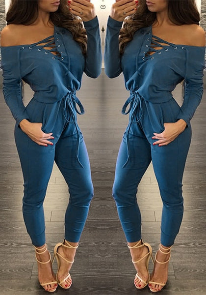 Mirror image of model in blue grommet lace up long sleeves jumpsuit