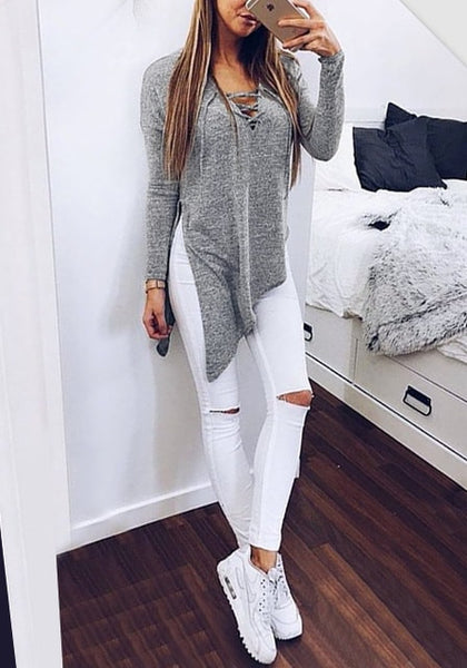 Model in a grey side-slit asymmetrical tee, white ripped jeans and white sneakers