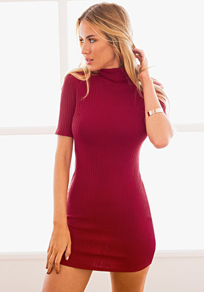 Model in a red ribbed turtleneck bodycon dress