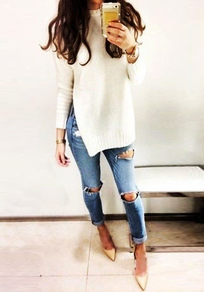 Model in beige side slit tunic sweater and distressed jeans