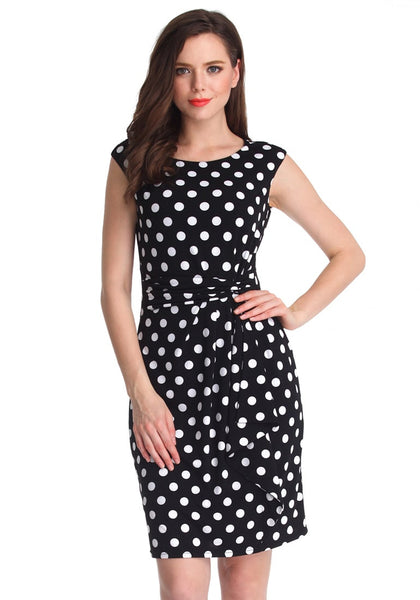 Model in black polka dot sleeveless dress poses with one hand on hip