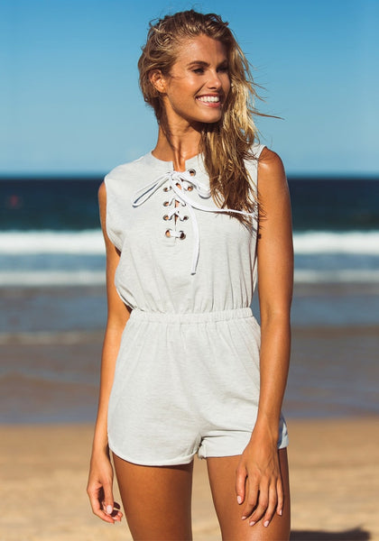 Model  in grey sleeveless lace-up romper on the sand