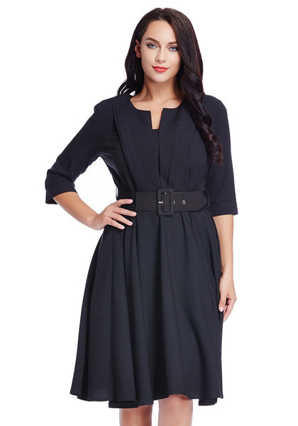 Model in plus size black belted skater dress has one hand on hip