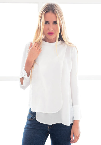 Model in white asymmetric layered chiffon blouse with one hand touching hair