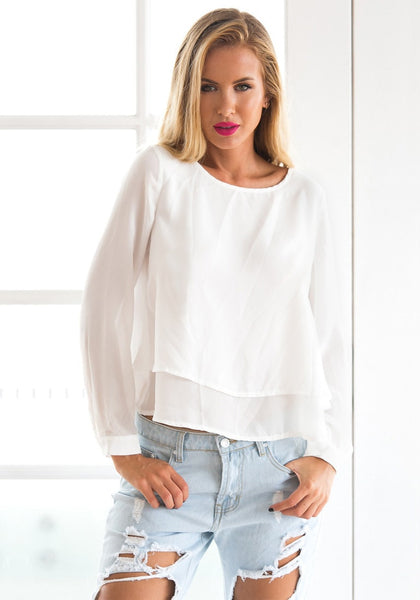 Model in white layered chiffon blouse and jeans