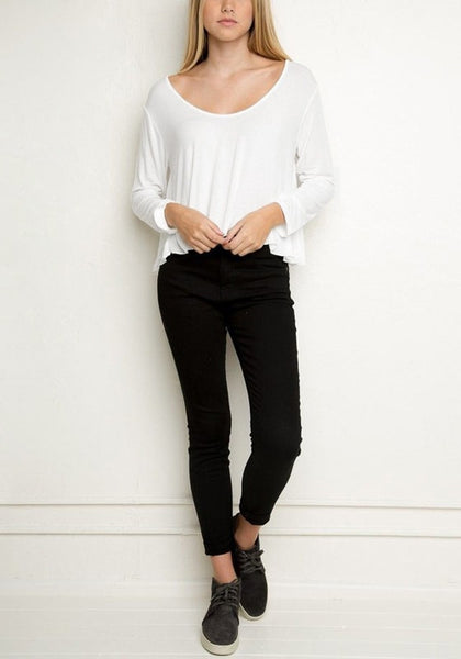 Model in white loose high-low tee, black pants and laced sneakers