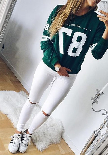 Model in white ripped skinny jeans and green varsity sweater