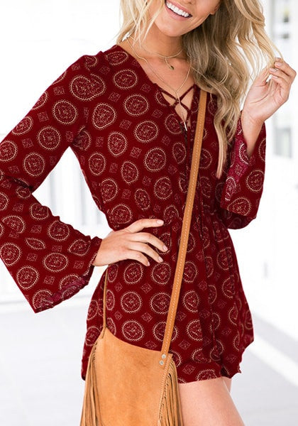 Model is wearing maroon lace-up trumpet sleeves romper and poses with one hand holding hair
