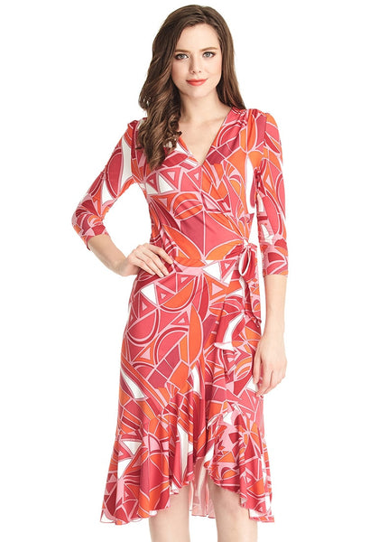 Model poses in abstract asymmetrical ruffled wrap dress with one hand on hip