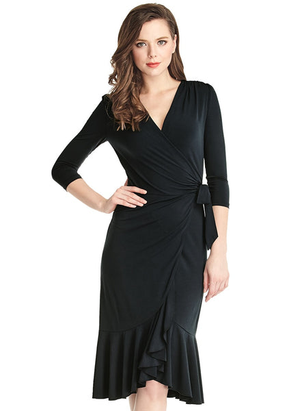 Model poses in black asymmetrical ruffled wrap dress with one hand on hip