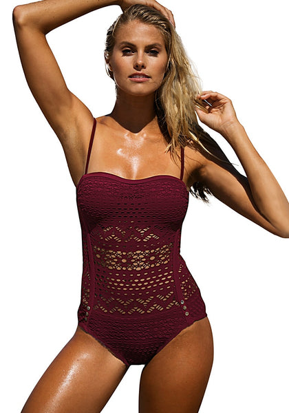 Model poses in dark burgundy lace halter swimsuit with one hand on head