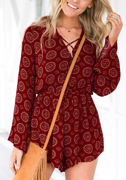 Model poses in maroon lace-up trumpet sleeves romper with one hand holding hair