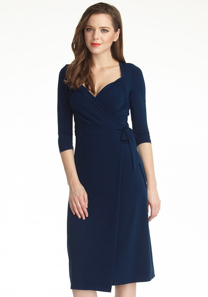 Model with navy blue sweetheart neckline wrap dress tilts head to the right