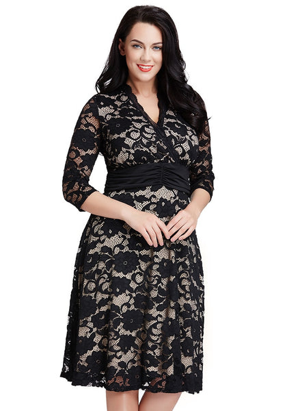 Model poses in plus size apricot lace surpliced ruched-waist dress with both hands in front