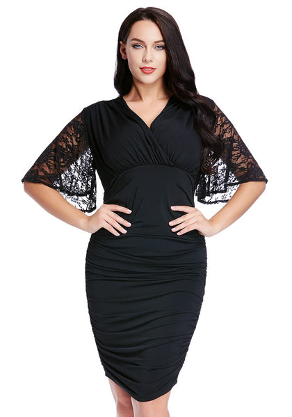 Model poses in plus size black ruching bodycon dress with both hands on hips