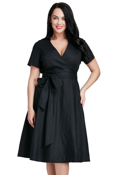 Model poses in plus size black surplice midi dress with one hand on hip
