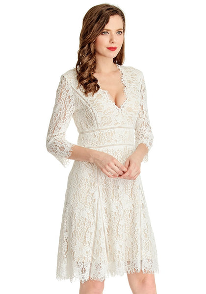 Model poses in slight right angle wearing white lace overlay plunge dress
