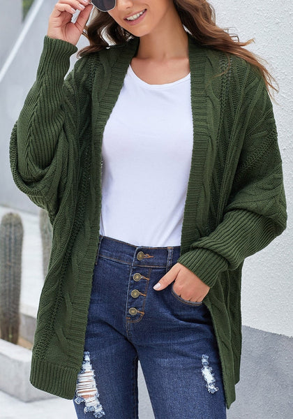Model poses wearing army green open-front oversized cable knit cardigan