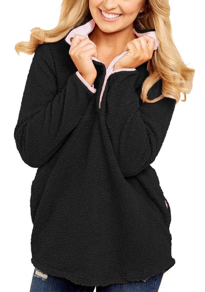 Model poses wearing black button-front pullover
