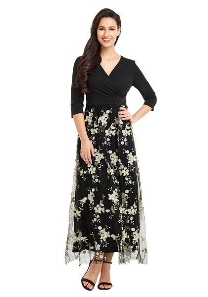 Model poses wearing black floral-embroidered mesh maxi dress